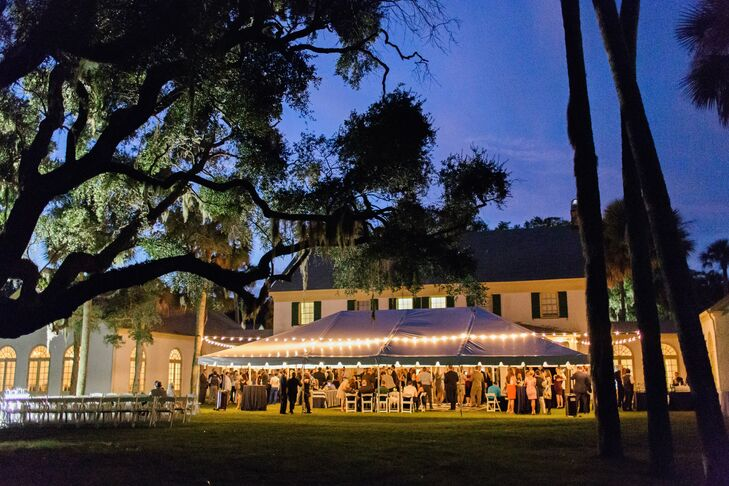 The reception was held outside, beneath a large open-sided tent hung with bistro lights.