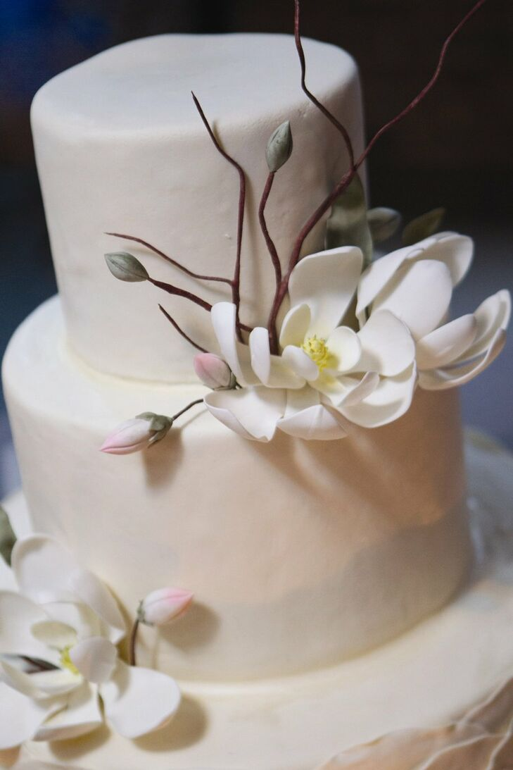 The orange-clove flavored cake, with wild honey buttercream, was decorated with a dramatic sugar magnolia flower between the top tiers.