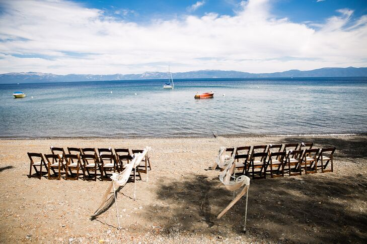 Jennifer and Gregory were married on the sand at the waterfront of Lake Tahoe, with minimal decorations to highlight the beautiful natural landscaping. Ribbon and lace draped over white iron hooks that lined the aisle, which held up hanging glass jars filled with wildflowers.