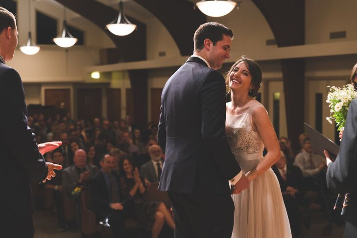 The couple stood at the front of the altar during their ceremony at Emmanuel Presbyterian Church in Thousand Oaks, California. Beth wore a simple pair of silver dangling earrings with her stunning lace-accented dress on the day of the wedding.