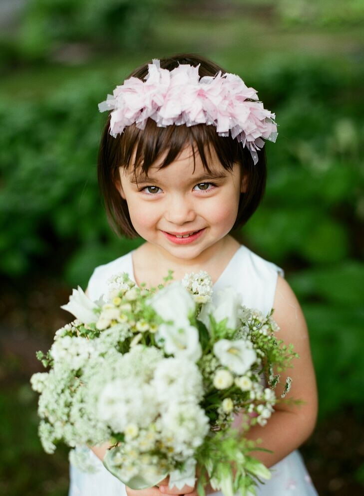 The flower girls wore gray and pink, and carried flowers that matched the bridesmaid bouquets.