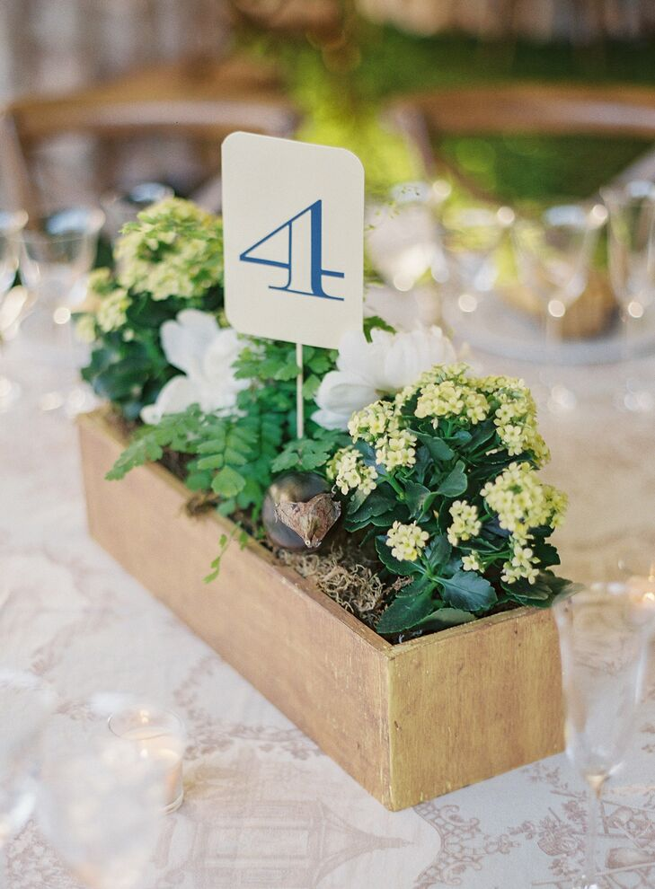 Ayse and Jack's centerpieces alternated between painted pots and wooden flower boxes, all filled with mixed seasonal flowers and a graphic table number.