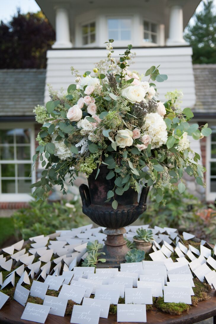 Dragonfly Events left no detail overlooked, creating sophisticated, statement-making arrangements of eucalyptus, roses, hydrangeas and ranunculus displayed in stately stone urns for the escort-card table and ceremony aisles.