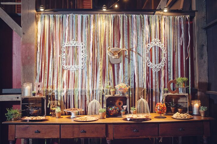 In lieu of a traditional wedding cake, Erin and Cory had a candy bar fit for a photo opp! Dogwood Events accented a vintage wooden desk with tiered baked goods, cookies and glass bowls filled with candy. Streamers, vintage-style frames and antlers formed the backdrop for an unexpected touch.