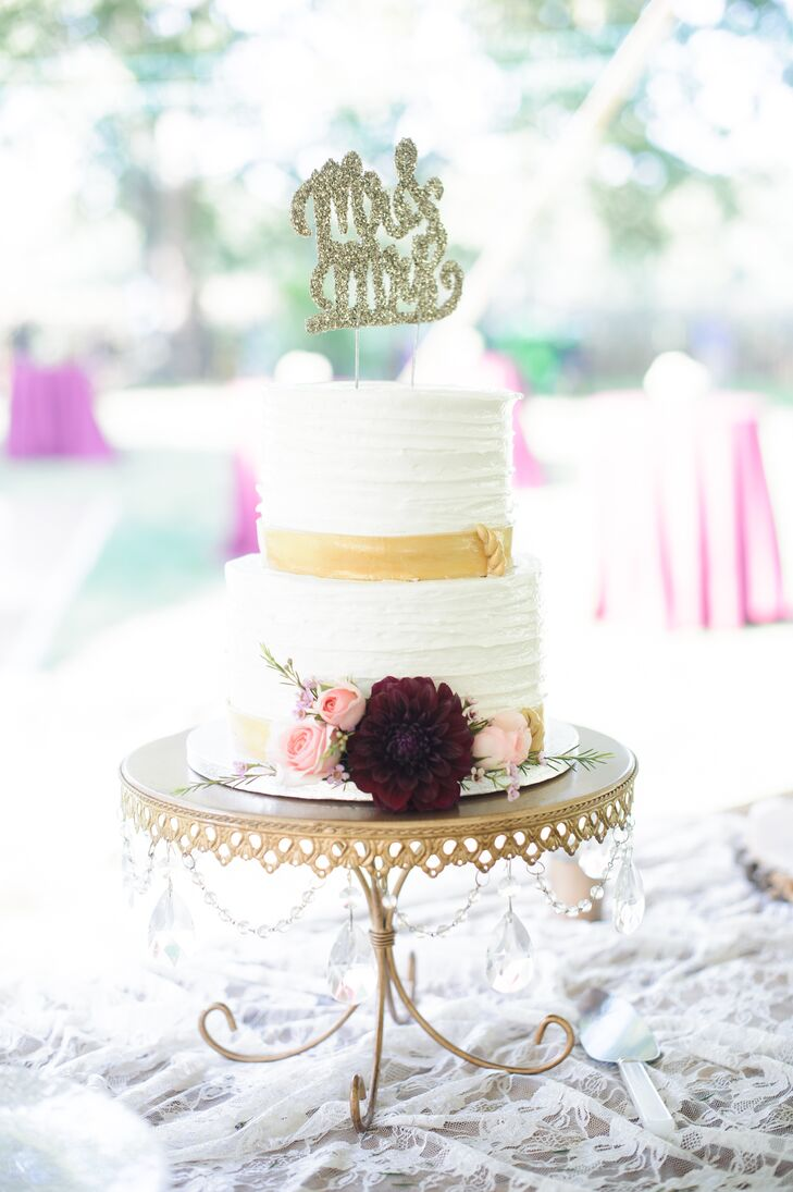 Placed atop a romantic pedestal dripping with crystals, the white icing, salted-caramel-center cake was decorated with gold accents and pink and wine-colored florals.