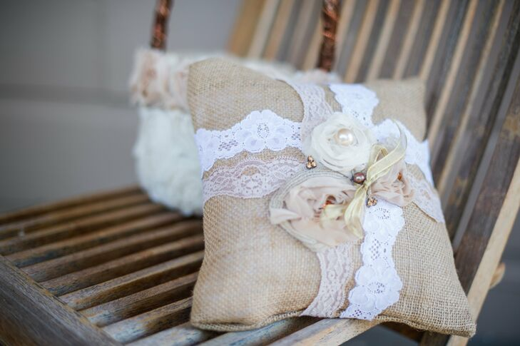 The ring bearer escorted the wedding bands down the aisle propped on a lace-wrapped burlap ring pillow.