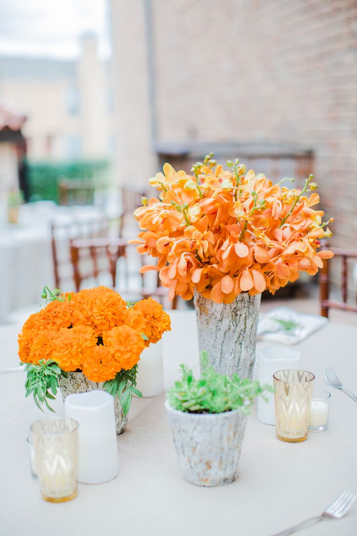 Vibrant orange flowers such as marigolds and orchids in natural birch-wood vases, surrounded by gold votives, added to the organic atmosphere at Alison and Pierce's alfresco courtyard reception at the Gallery in Houston, Texas.