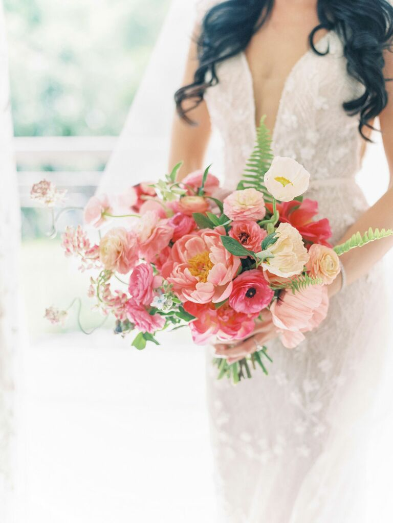 Bride holding bouquet of pink and blush peonies