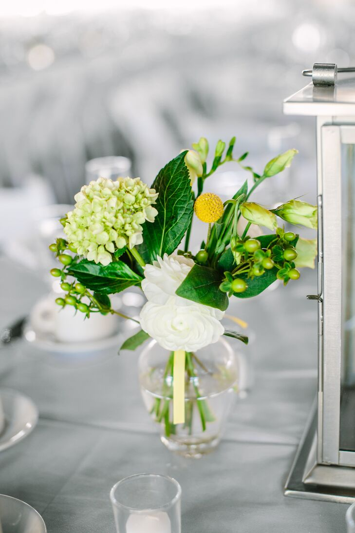Lynn and her bridesmaids designed all of the centerpieces for the reception, using flowers like ranunculuses, hydrangeas, lisianthuses, scabiosas, craspedias, freesias and more from fiftyflowers.com. The understated arrangements added an air of freshness and a subtle pop of color to the chic, modern tablescapes, while silvery lanterns filled with ivory candles cast a warm, inviting glow over the space.