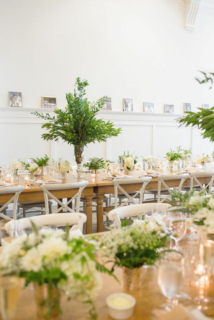 """The tablescape was set along two long wood tables, dressed only with a white linen table runner,"" Emily says. ""Tablescapes comprised of two alternating floral arrangements and a plethora of mixed gold, pewter, mercury glass and cut glass candle holders."""