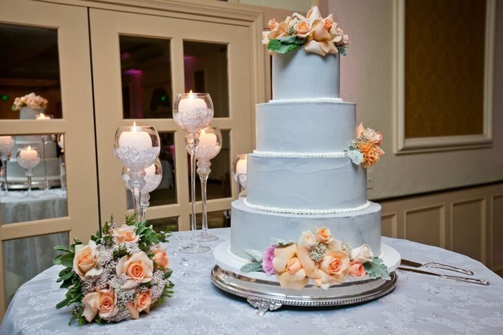The four-tiered gray cake was accented with fresh peach roses.