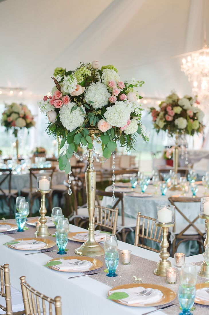 The couple decorated their reception in shades of gold, blue and white. Some of Erica and Cole's family style tables were decorated with tall arrangements of blush garden roses, white and green hydrangea, pink roses and eucalyptus atop a gold stand. Crystal accents were hung from each arrangement.
