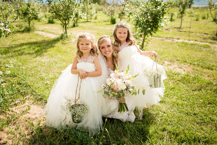 """The two flower girls wore these ivory tutu dresses. Leslie's friend made the dresses for the occasion. """"The girls looked like little clouds and were so happy in their poofy princess dresses and ballet slippers,"""" Leslie says. They completed their look with baby's breath flower crowns."""