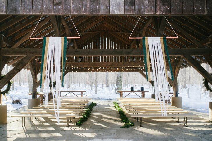 Under the wooden pavilion at Thorpewood in Thurmont, Maryland, long green garlands lined both sides of the ceremony aisle. Guests entered the space in between two cream-colored canvas curtains hanging from the ceiling.