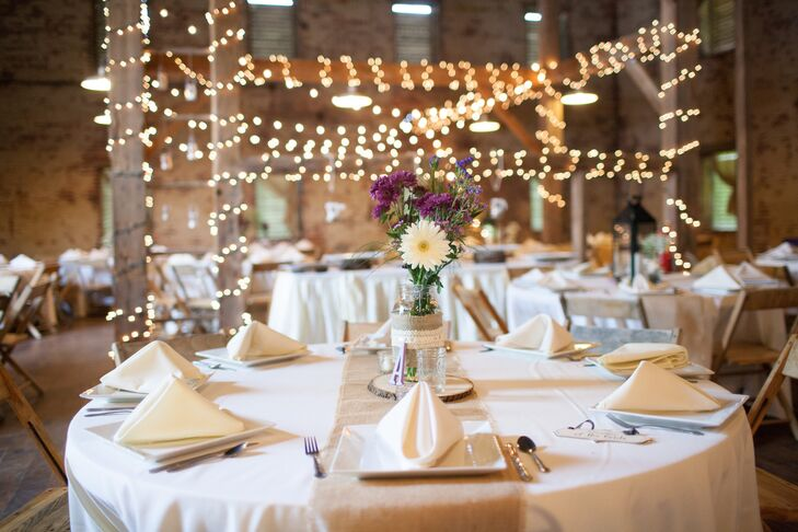The barn reception featured exposed-brick walls and wooden beams that were decorated with string lights. Dining tables were arranged with white linens and burlap table runners.