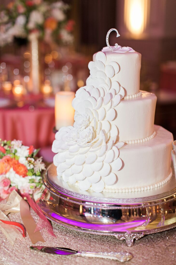 "A three-tier cake embellished with a large flower was topped with a small Swarovski crystal ""C"" for Combs."