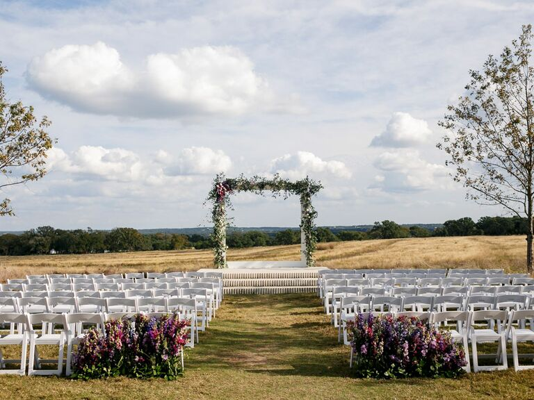 Casual outdoor wedding venue with white seats and rectangle floral arch