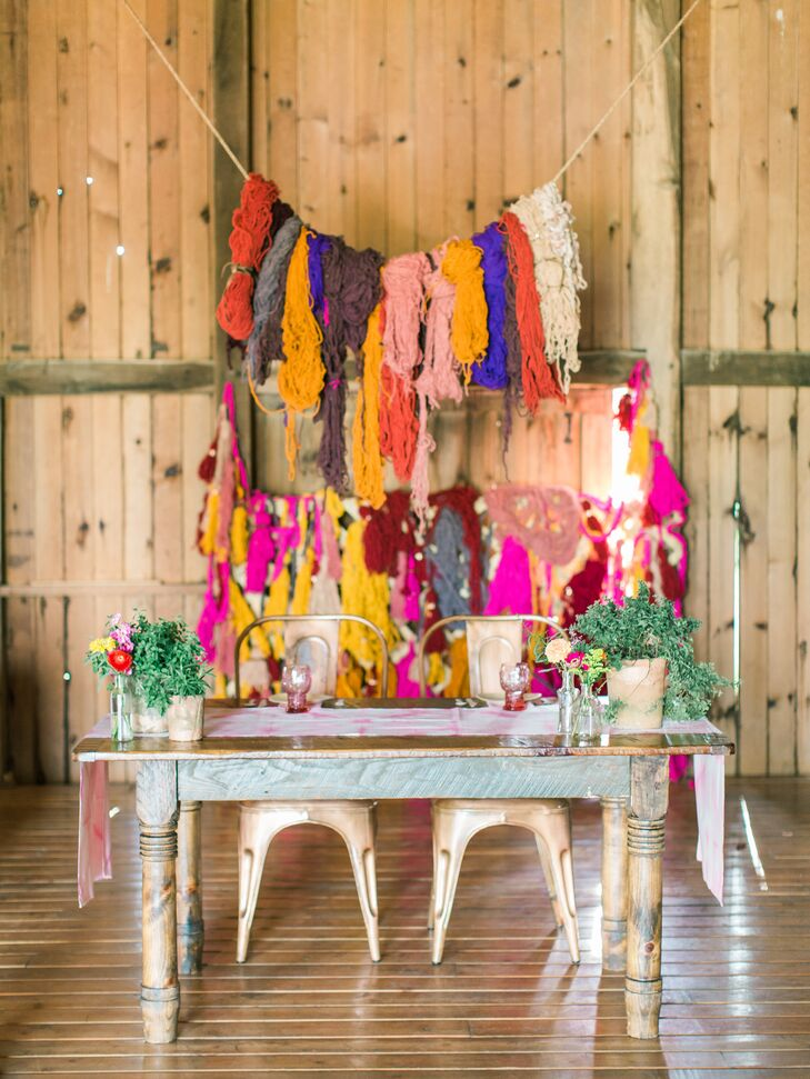 """A large yarn display strung behind the sweetheart table added a homespun vibe to the couple's bold, bohemian-inspired decor. """"We wanted our wedding to stand out from the norm and for our guests to feel an overwhelming sense of cheer and happiness,"""" Courtney says."""