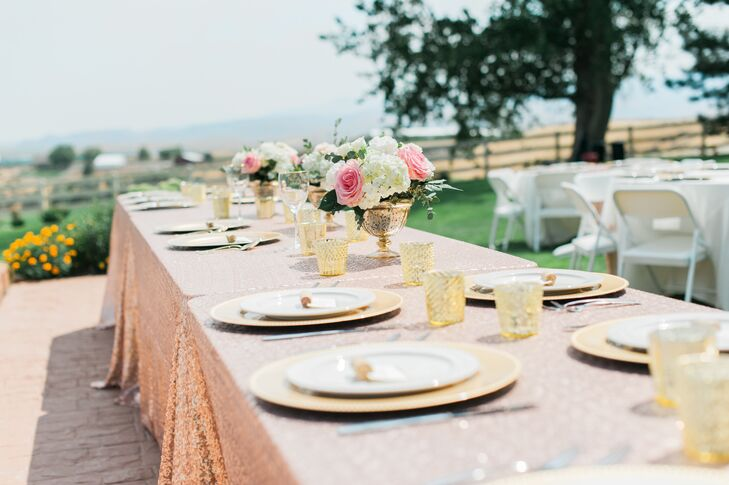 """The centerpieces were gorgeous, small arrangements in blush and ivory flowers in gold mercury vases,"" Amber says. ""I made gold and ivory table numbers. The guest table had ivory tablecloths, blush sequin table runners, ivory plates and napkins and gold charger plates. Everyone sat wherever they wanted, but I had names on each plate at the head table, which I made printing gold names onto ivory card stock and using corks to hold them up."""