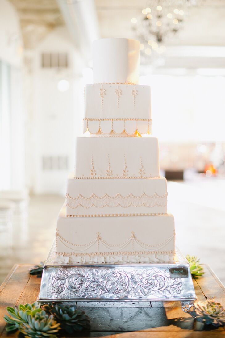 Annie and Matt went classic when it came to their cake, choosing a simple, elegant design with square tiers, ivory fondant and dainty, decorative piping. The pair chose three decadent flavors for guests to choose from, including chocolate, vanilla and carrot cake.