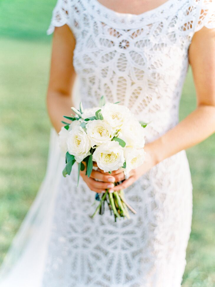 """When it came to the bouquets, simplicity was essential. """"I love the look of a petite arrangement and didn't want to feel overwhelmed by an enormous bouquet,"""" Christine says. To accompany her Rue de Seine gown, Birds of a Flower pulled together a pint-size arrangement of ivory garden roses accented with bright green eucalyptus."""