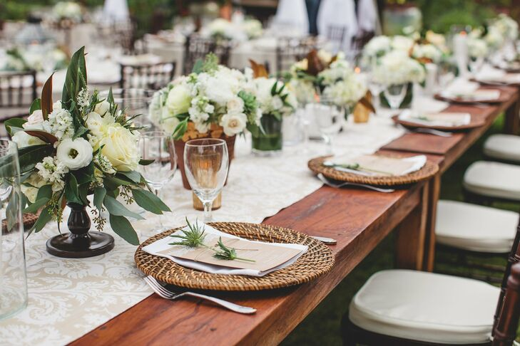 Napkins and menu cards rested on rattan chargers, which were placed on long wooden reception tables. Tan and white table runners and low centerpieces filled with hydrangeas, roses and flat-leaf eucalyptus allowed plenty of room for conversation to flow.