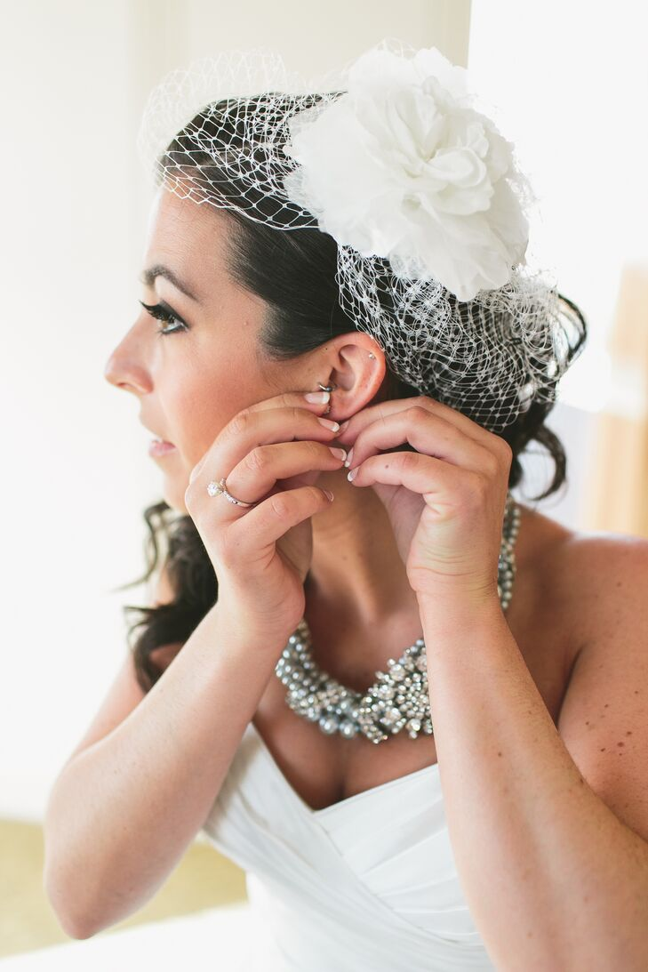 Kaitlyn incorporated the vintage style that inspired their wedding theme into her own look with a white netted birdcage veil, topped with a white fabric peony flower.