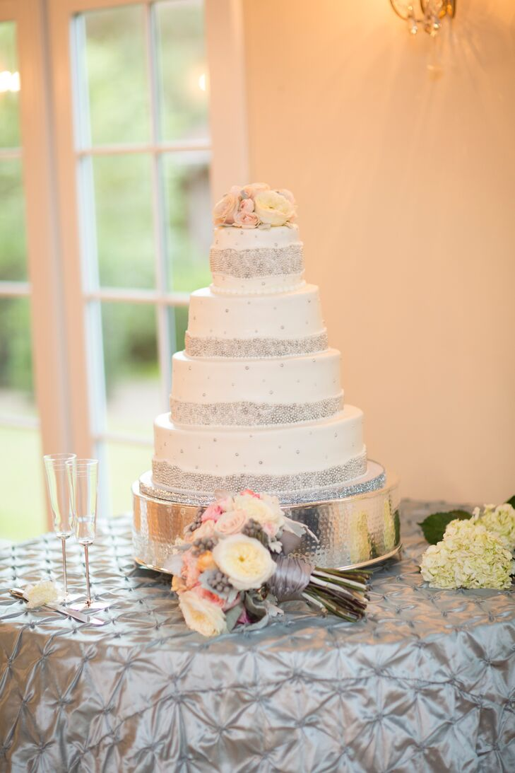 The white wedding cake was decorated with bands of silver dragees as well as pink roses and white ranunculuses.