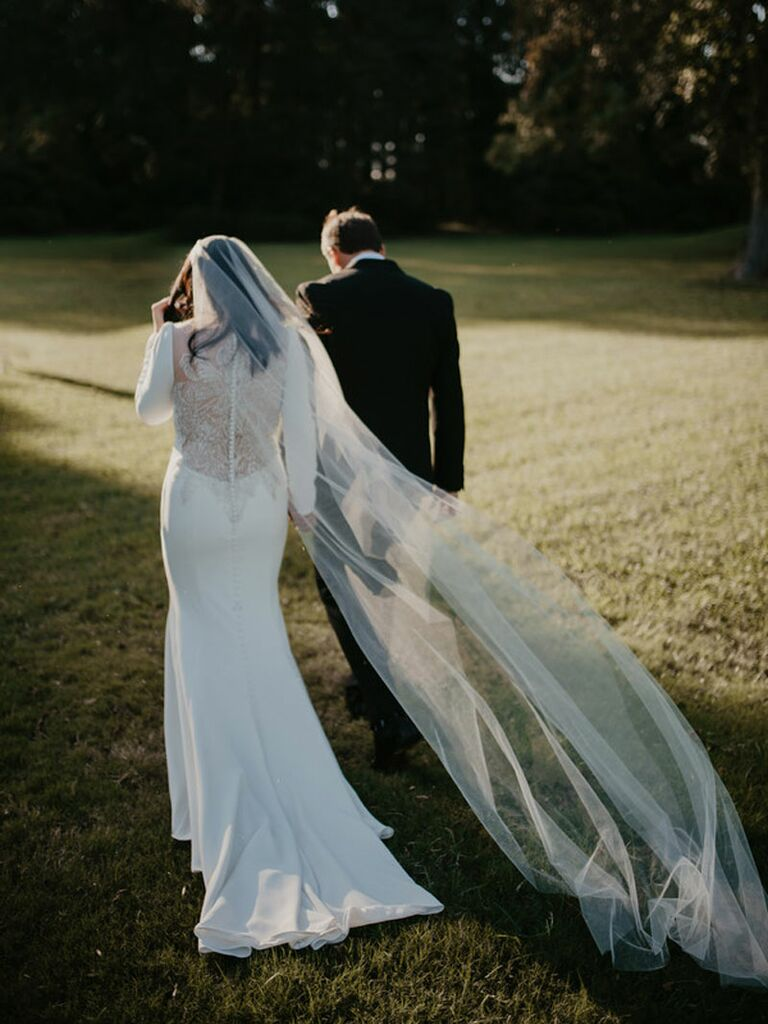 Groom and bride walking on wedding day with veil trailing in the wind