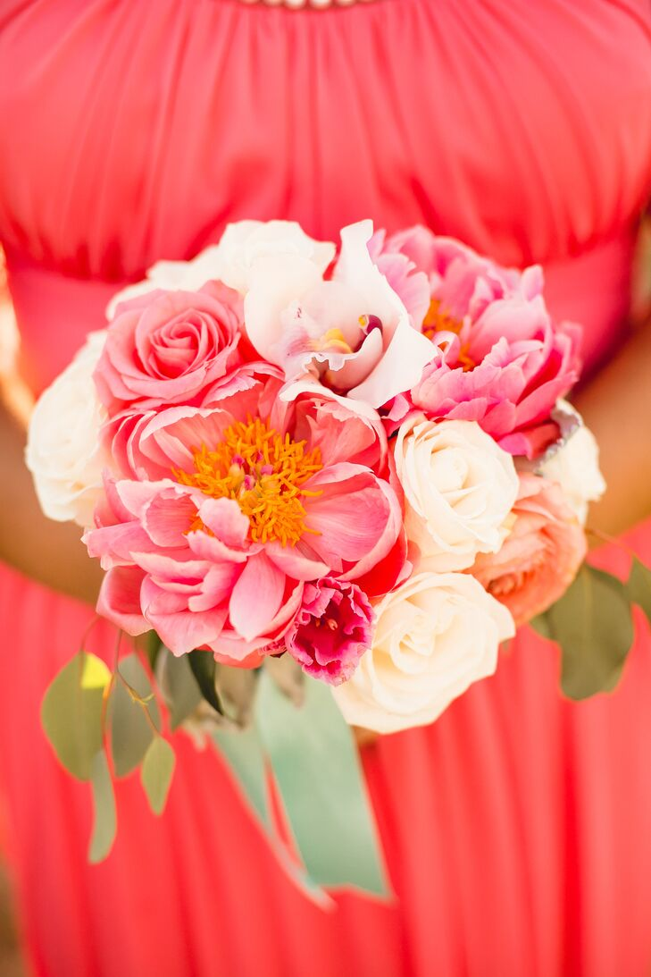 """Veronica and her bridesmaids held matching white and coral bouquets, filled with roses, lilies and peonies (her favorite flower). """"When it came to flowers, I really loved the look of peonies and knew I wanted to include them in our bouquets and centerpieces,"""" Veronica says. """"I wasn't too specific with the florals other than requesting the peonies, but I let the florist work her magic and everything came out better than I could imagine."""""""