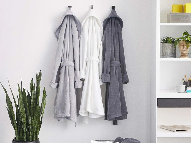 Three cotton bathrobes hanging on the wall in different hues