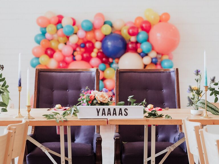 wedding sweetheart table with balloon backdrop and greenery