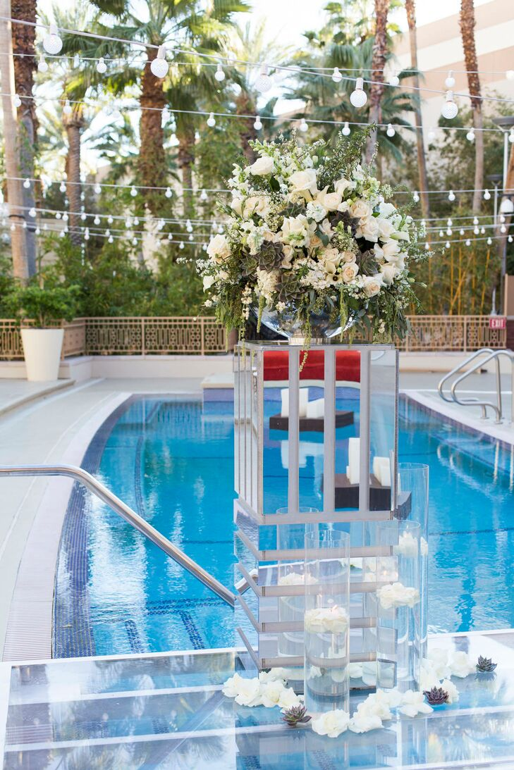 The interior space at Crimson featured red roses and black calla lilies. The exterior space, next to the pool, had peach and ivory roses and succulents were added to wooden planters on each table.