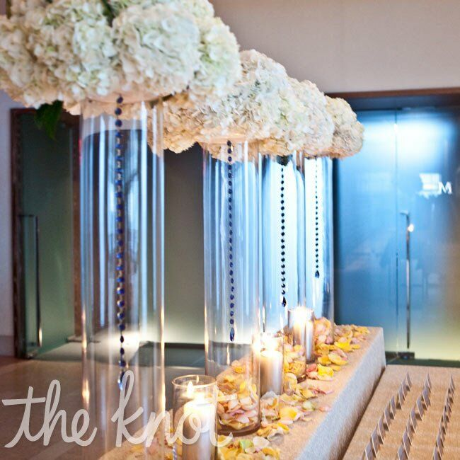 Tall cylinder vases filled with pomanders of white hydrangeas were the focal point of the escort card table.