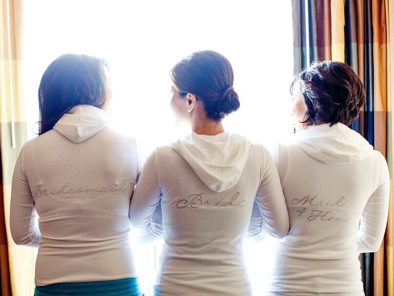 Bride and bridesmaids in matching white hoodies