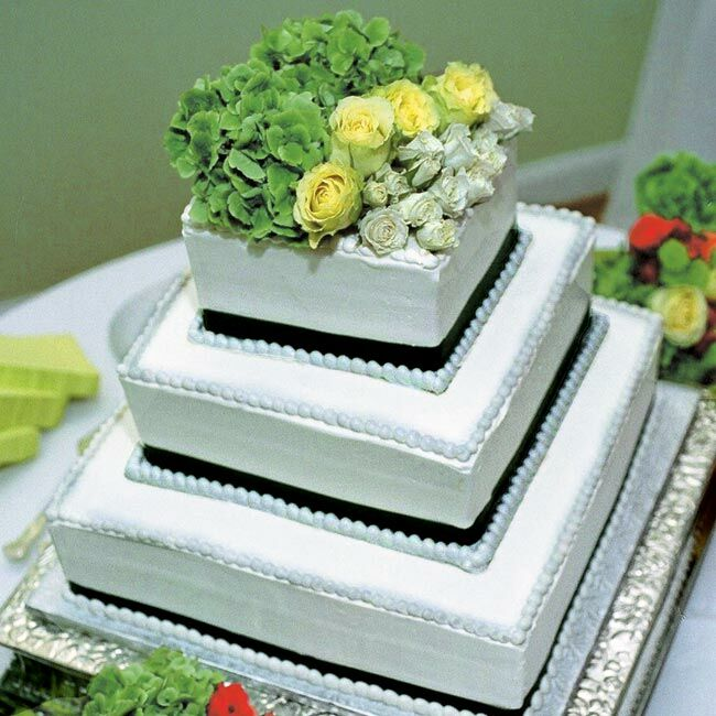 Diane and Scott's cake was a four-tiered yellow cake covered with white buttercream frosting, wrapped with a green grosgrain ribbon, and topped with various green flowers. The groom's cake was all chocolate and covered with chocolate shavings and strawberries.