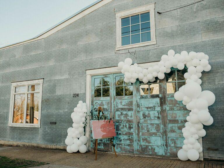White balloon arch around entrance at industrial wedding reception venue