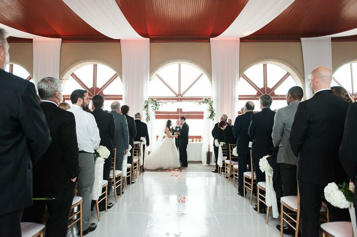 Kathleen and Alan planned to exchange vows outside, but they had to move inside because of the weather. They decorated the venue with white drapery on the ceiling to create a more intimate, chic aura. The linens were lit with a warm candlelight hue that got brighter as the night progressed.