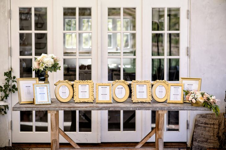 A wooden table that gave off a rustic flair contrasted with the gold-framed seating assignments, where guests could find their designated spot for the reception. The table was accented with neutral-colored flower arrangements in gold vases, which matched the dining-table centerpieces.