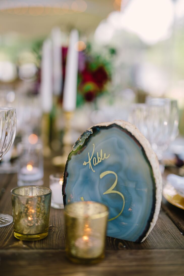 Eclectic agate table numbers inscribed with gold calligraphy adorned each dining table. Gold mercury glass votives continued the glam pop of color.