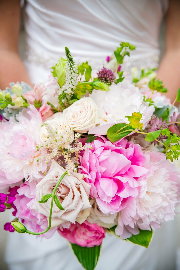 """Callie's mother and mother-in-law let her use pieces of lace from their veils to wrap around her bouquet, which served as her """"something old."""" Peonies, white hydrangeas, English garden roses, ranunculus and dusty miller were all used at Callie's request."""