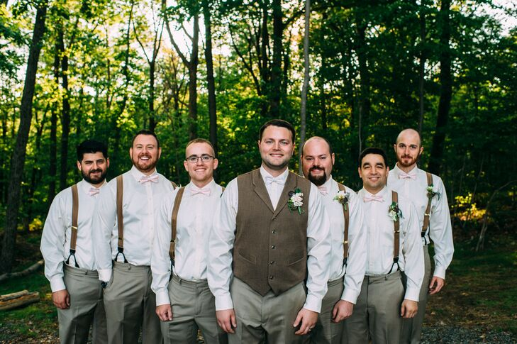 What a fun, casual look! Taking a tip from Nick's neutral look, all six groomsmen donned white shirts and gray pants from Men's Wearhouse. The neutral suspenders and blush bow ties made it slightly more formal, while their white, natural boutonnieres hinted at the scenery. Nick stood in front of them with a neutral vest from the Gentlemen's Emporium and white bow tie.