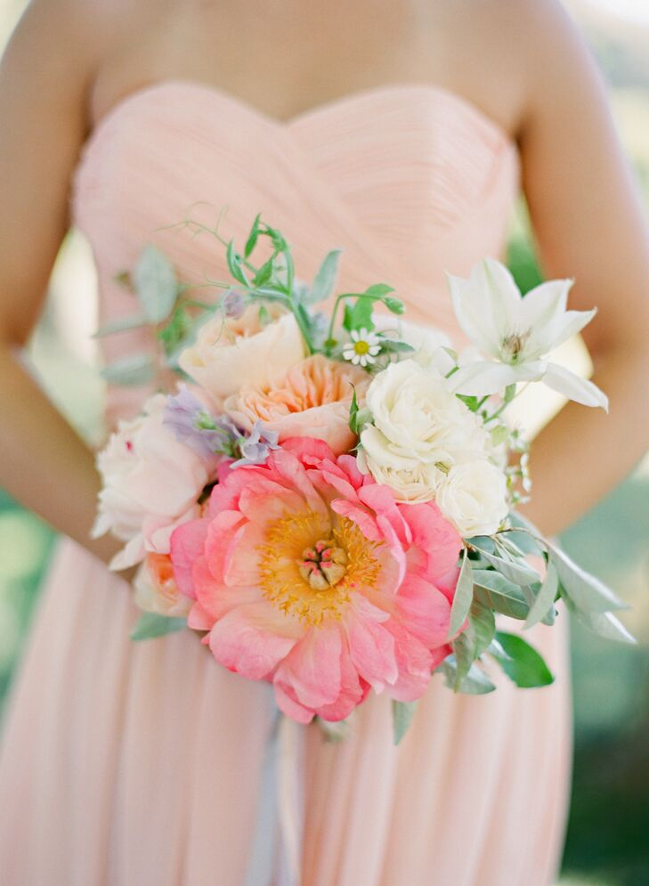 The bridesmaids carried bright bouquets of peonies, roses and sweet pea in shades of pink, purple and white. Wispy greenery lent a whimsical air to each garden-inspired bouquet.