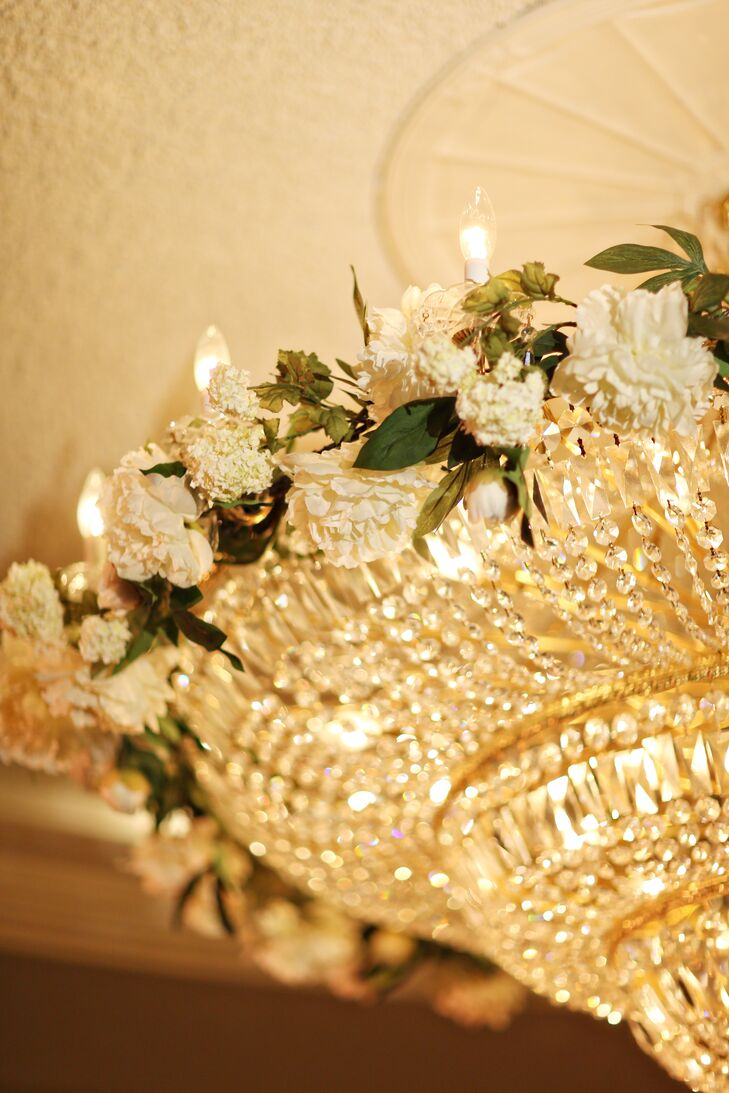Instead of putting up flower chandeliers, Kieran and Tom decorated the crystal chandeliers at the Overbrook ballroom with garlands of white carnations, white hydrangeas and greenery. The flowers literally glowed as they hung above the party.