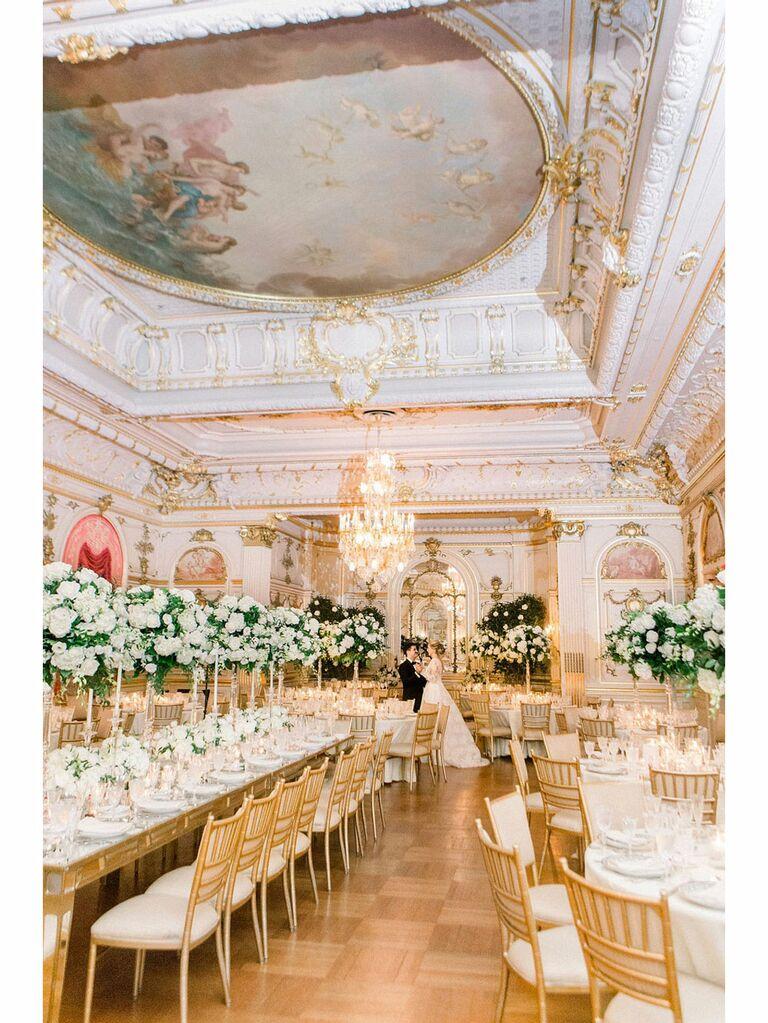 Bride and groom posing in opulent regencycore wedding reception venue
