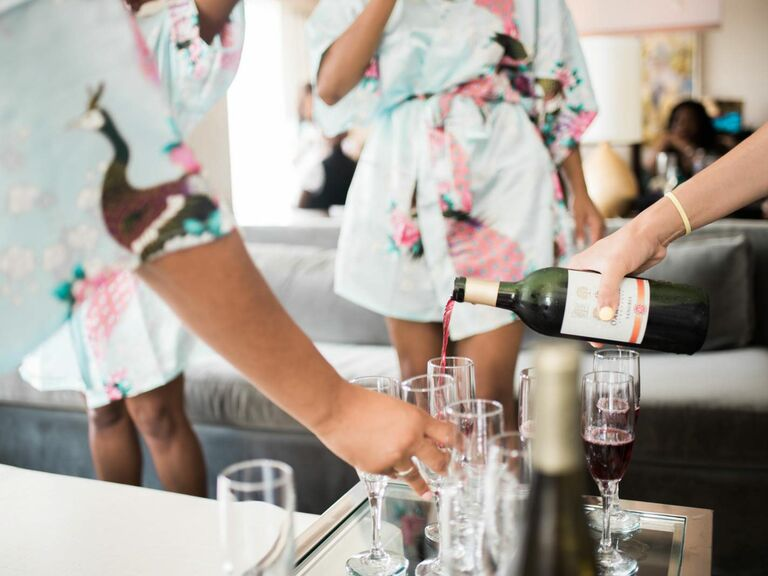 Bridesmaids getting ready and drinking pink champagne