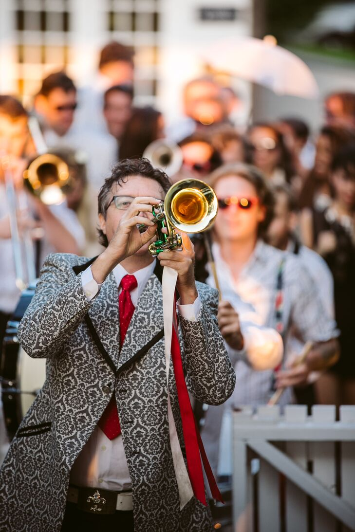 "Jill and Conor decided to kick off the evening's festivities with a bang with a surprise entrance at the reception. A lively New Orleans-style brass led the newlyweds and their wedding party second line style onto the Easton Hampton Point's deck to the beat of ""When the Saints Go Marching In."""