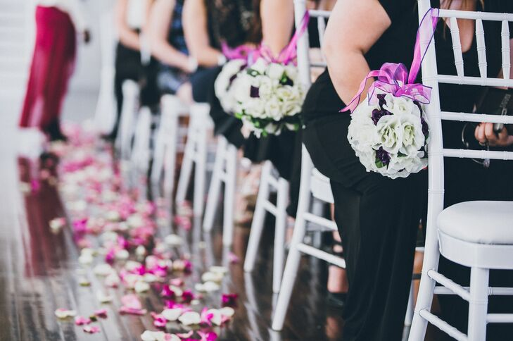 Floral pomanders hung on fuchsia ribbon to decorate the white chiavari chairs lining the aisle during the ceremony.