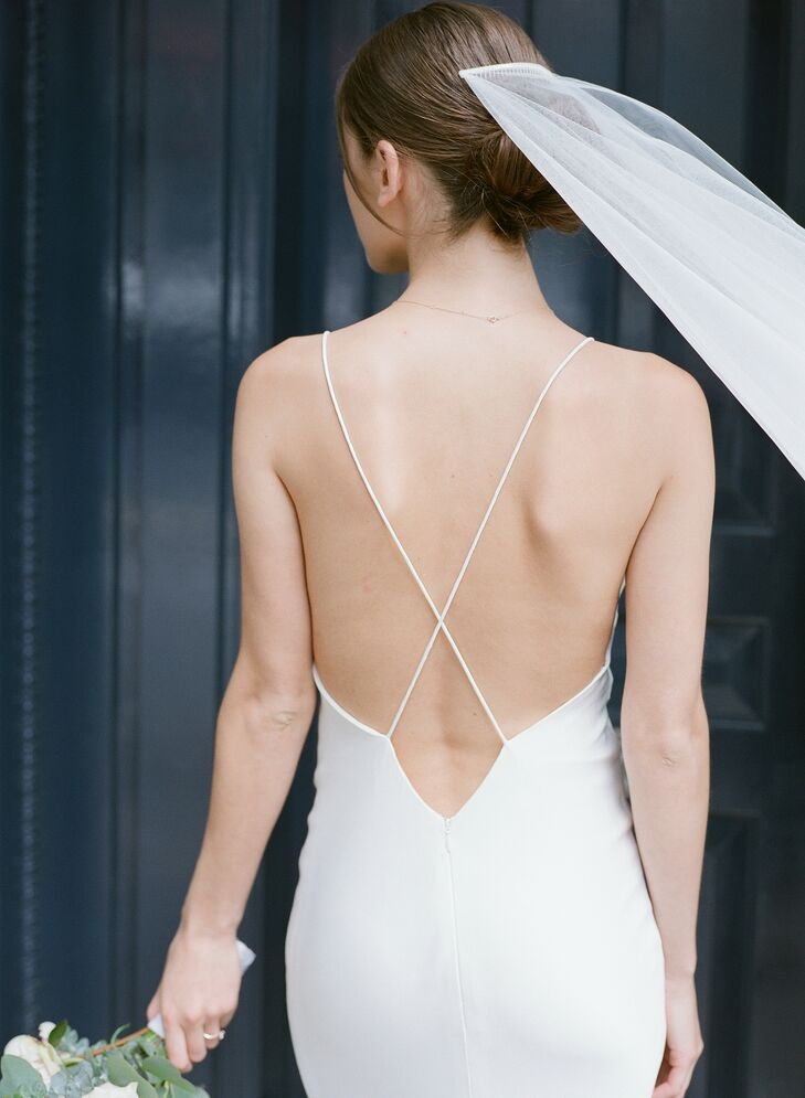 Bride Wearing Modern Form-Fitting Wedding Dress with Cross-Back Straps, Updo and Veil