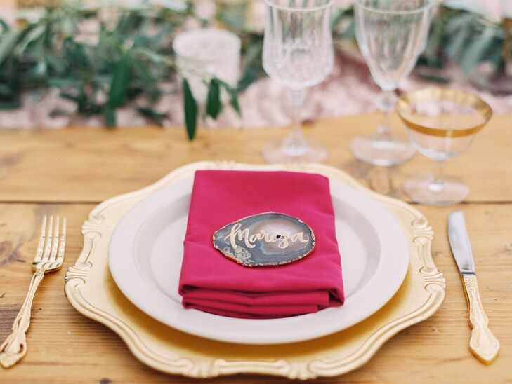 Each setting was marked by an elegant flat rock with the guest's name written in gold. The seating assignment rested on top of a fuchsia napkin, along with the white and gold plates used for the evening's meal.